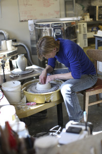 Julie Anderson in her studio throwing porcelain on the wheel